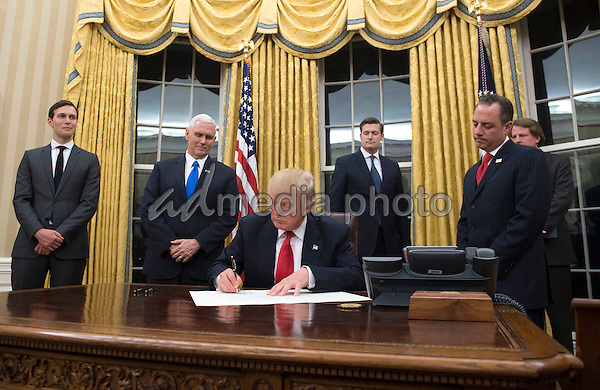 President Donald Trump prepares to sign a confirmation for Homeland Security Secretary James Kelly, in the Oval Office at the White House in Washington, D.C. on January 20, 2017. Photo Credit: Kevin Dietsch/CNP/AdMedia
