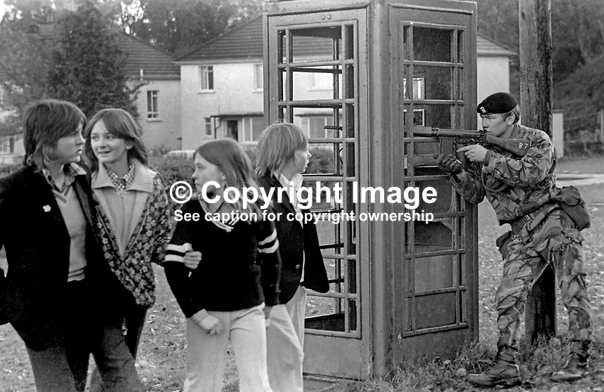 Normality in Belfast - a soldier with his rifle at the ready barely merits a glance from four young girls walking past him during a lull in rioting in the Roman Catholic Lenadoon estate in West Belfast, 9th July 1972. 197207090379a<br />