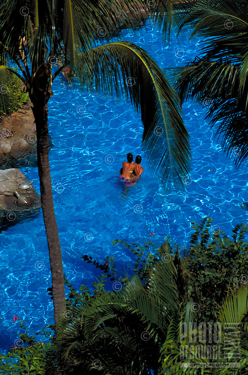 Young couple playing in pool surrounded by palm trees at a tropical resort on Oahu.