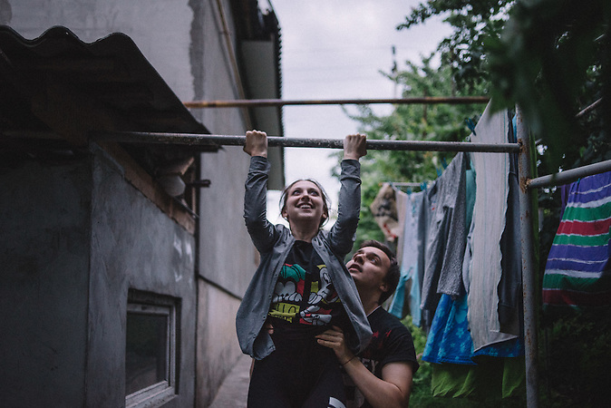 Alexander helps Katrine to pull up at courtyard of her parents house. Ribnita, Transnistria