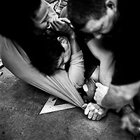 A man is pinned down in a two-on-one bare knuckle fight..'Gentlemen's Fight Clubs' are held in private garages or homes. People who work as software engineers and programmers during the day meet there to fight. This way they are able to let out their tensions, frustrations and passions in somtimes overtly violent ways. The participants are known to use keyboards, dustbusters and rolled up women's magazines in their fights. Silicon Valley, California.