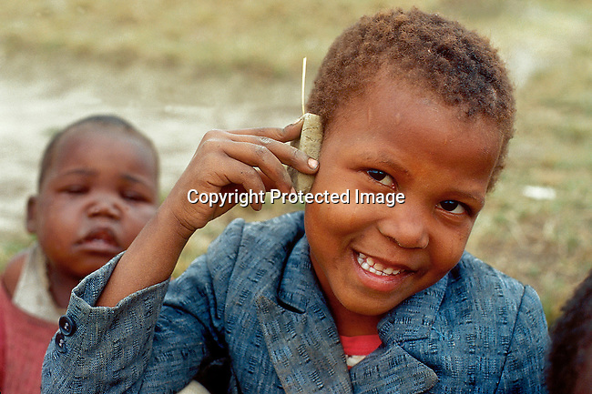 PPCHILD50354.People.  Children.  Kwazulu-Natal.  Smiling young black child holding a homemade phone to his ear.  Another black child in background.  99..©Per-Anders Pettersson / iAfrika Photos