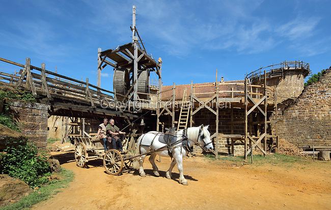 Cart pulled by a horse transporting building materials, and behind, scaffolding on the curtain walls and lifting gear with double drum squirrel cage, an early form of crane, at the Chateau de Guedelon, a castle built since 1997 using only medieval materials and processes, photographed in 2017, in Treigny, Yonne, Burgundy, France. The Guedelon project was begun in 1997 by Michel Guyot, owner of the nearby Chateau de Saint-Fargeau, with architect Jacques Moulin. It is an educational and scientific project with the aim of understanding medieval building techniques and the chateau should be completed in the 2020s. Picture by Manuel Cohen