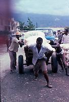 Man handling cart full of food sacks. Images of the capital,Port au Prince, Haiti 1975