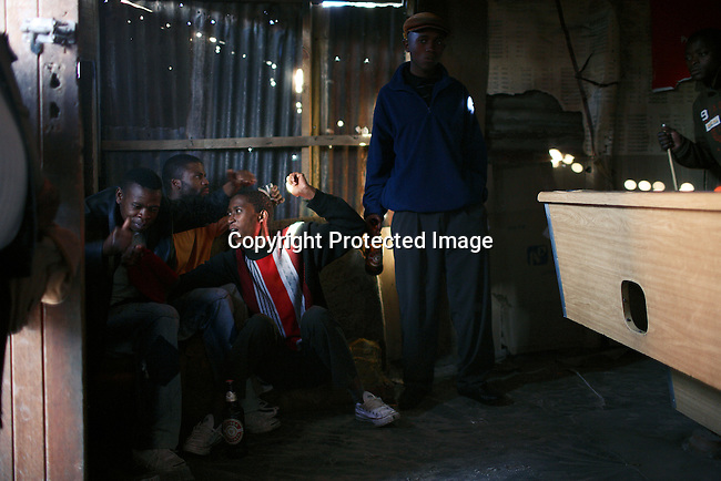 Unemployed men party in the middle of the day in a bar in a poor squatter camp in Guguletu outside Cape Town.  Photo by: Per-Anders Pettersson/Getty Images for Smithsonian Magazine.