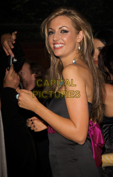ROSANNA DAVISON .Lambertz Schoko & Fashion Party, Age .Waiting room, Cologne, Germany..February 2nd, 2009.half length black dress pink waist belt looking over shoulder .CAP/PPG.©/People Picture/Capital Pictures