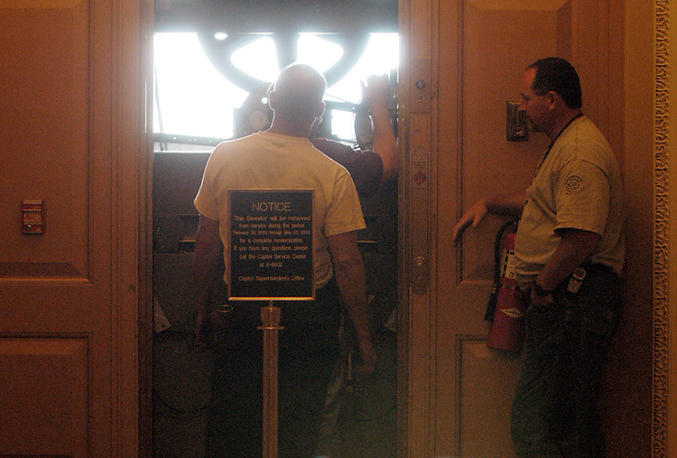 elevator052803 - Repair workers in the Capitol fix an elevator on the third floor of the Senate during the Memorial Day recess.