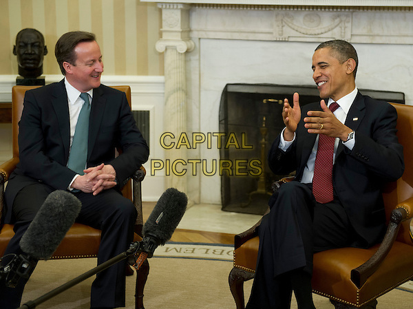 Prime Minister David Cameron of Great Britain and United States President Barack Obama meet in the Oval Office the White House in Washington, D.C. on Wednesday, March 14, 2012 following the Official Arrival Ceremony in Cameron's honor.  .full length black suit sitting side profile hands.CAP/ADM/RS.©Ron Sachs/Pool/CNP/AdMedia/Capital Pictures.