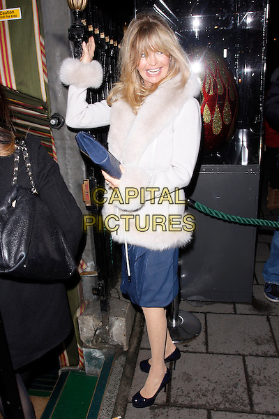 Goldie Hawn.The Hawn Foundation- fundraising gala, Annabel's, London, England..March 7th, 2012.full length white fur trim jacket coat suede blue clutch bag side hand arm waving .CAP/AH.©Adam Houghton/Capital Pictures.