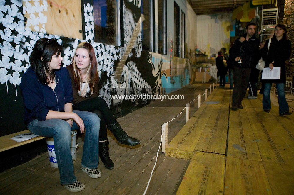 15 December 2006 - New York City, NY - Street artists Vanessa Bley (L) and Erin Green (2L) talk as people walk through a three-day street art exhibition held in a 19th-century brick building at 11 Spring Street in the NoLIta neighborhood of New York City, USA, 15 December 2006. The building's new owners, Caroline Cummings and Bill Elias, called on the Wooster Collective to curate the show as a last hurrah for a site that long served as a canvas for street art.
