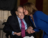 United States House Minority Leader Nancy Pelosi (Democrat of California), right, plants a kiss on the cheek of former US Senator Bob Dole (Republican of Kansas), left, prior to making remarks at a Congressional Gold Medal ceremony honoring Dole that was also attended by US President Donald J. Trump in the Rotunda of the US Capitol on Wednesday, January 17, 2017.  Congress commissioned gold medals as its highest expression of national appreciation for distinguished achievements and contributions.  Dole served in Congress from 1961 through 1996, was the Senate GOP leader from 1985 through 1996, and was the 1996 Republican Party nominee for President of the United States.<br /> Credit: Ron Sachs / CNP