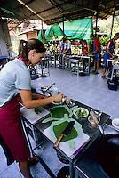 Female traveler preparing Thai food at cooking class, Chiang Mai, Thailand