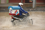 Undeterred by flooded roads and driving rain, a Dominoes Pizza man makes his lunch time delivery in a Guatemalan town.