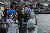TURKEY Istanbul , woman with headscarf fishing at Galata bridge/ TUERKEI Istanbul, Frau mit Kopftuch angelt an der Galata Bruecke