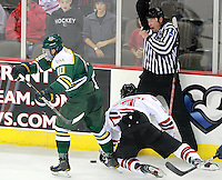 Linesman Chad Evers gets hit by a stick as Nebraska-Omaha's Terry Broadhurst and Alaska-Anchorage's Mickey Spencer battle for the puck. (Photo by Michelle Bishop) ..