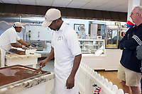 People watch as Daniel Ferguson, 50, (center), and Davian Miller, 24, make fudge at Murdick's Fudge in Edgartown, Martha's Vineyard, Massachusetts, USA. Ferguson is from Jamaica and has an H2B seasonal foreign worker visa. He says 2017 is his sixth summer season working in the fudge shop. During off-months, he returns to Jamaica where he can be with family and escape the cold weather. Miller has worked here for two seasons, and Scott for four seasons. Most of the shop's workers are seasonal foreign workers. Other companies on Martha's Vineyard and around the US had difficulty obtaining H2B visas, but Murdick's Fudge received all it requested.