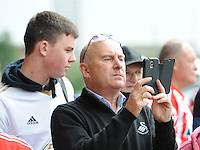 A Swansea fan films the team bus arriving during the Barclays Premier League match between Sunderland and Swansea City played at Stadium of Light, Sunderland