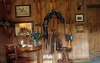 The small desk in the living room is surrounded by photographs of horses and a collection of wall-mounted saddle racks