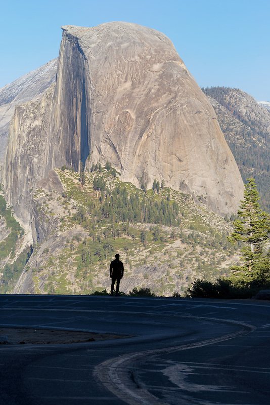 Hiker silhouette in front of Half Dome. Yosemite National Park, CA