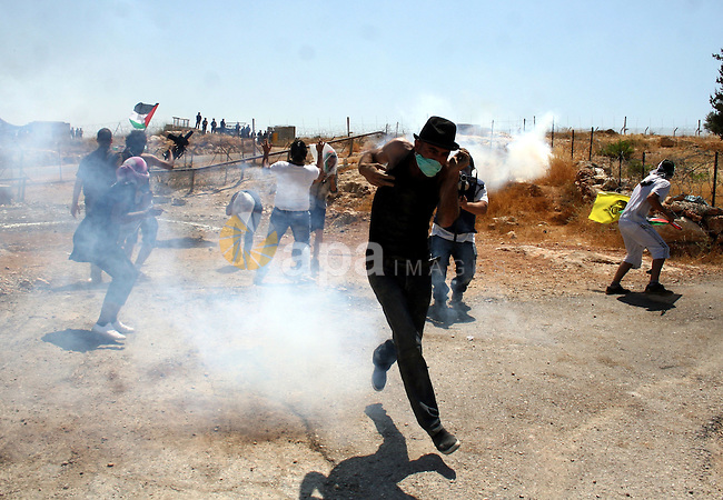 Protestors run amidst tear gas smoke fired by Israeli forces during clashes following a weekly demonstration against Israel's separation barrier in the Palestinian West Bank village of Bilin on June 17, 2011. Photo by Issam Rimawi