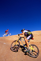 Male mountain bikers climbing a very steep sandstone hill on the famous Slickrock Trail, Moab, Utah