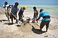 Council workers fill sacks with concrete mix that are then stacked forming sea walls that protect the atoll from high tides concurring with storm surge.