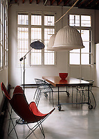 Huge pendant lights hang over the dining table in this converted factory