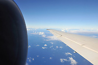 Wing and jet engine of airplane flying over Pacific Ocean, Hawaii Islands, Usa
