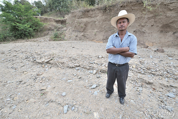 Pedro Rodolfo Orteaga, a small farmer, stands on the bed of a river that has gone dry since a Canadian mining company installed a gold mine in the area and has monopolized the area's water, leaving small farms and riverbeds dry. Orteaga is a member of a group of area residents that oppose the mine's activities.