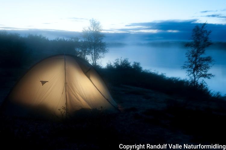 Teltleir ved vann en sommernatt. ---- Tent by lake.