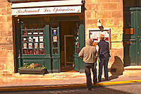 The restaurant Les Epicuriens in the medieval village Saint Emilion, Bordeaux. People tourists reading the  menu outside