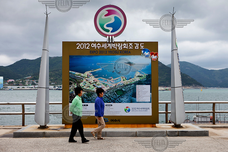 People walking on Odongdo Island which is connected to the mainland by a 768 metre long breakwater. They are passing walking a map of the Expo 2012 site held in Yeosu with the theme The Living Ocean and Coast'.