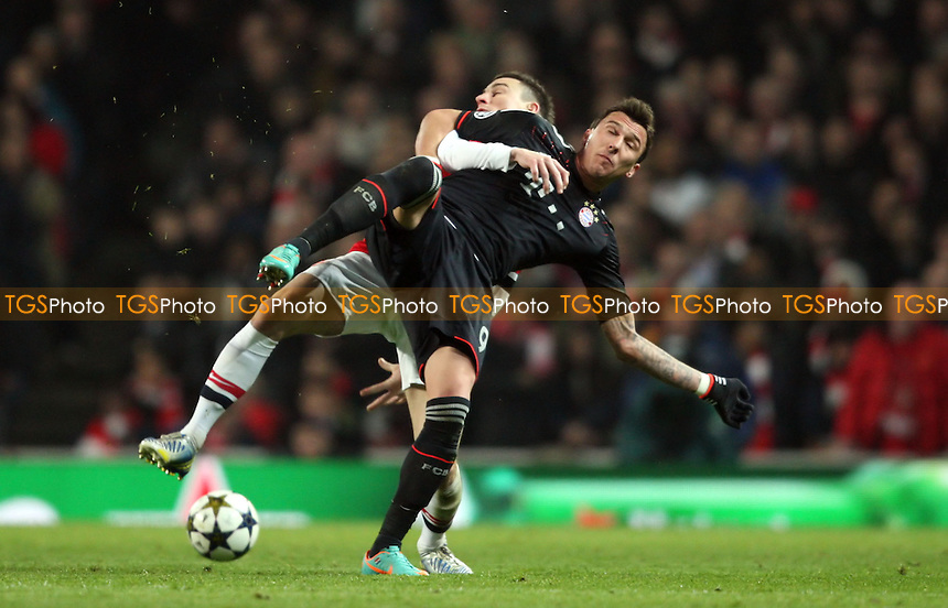 Mario Mandzukic of Bayern Munich and Laurent Koscielny of Arsenal - Arsenal vs Bayern Munich, Champions League 1st Knock Out Round, 1st Leg at Arsenal Stadium, Arsenal - 19/02/13 - MANDATORY CREDIT: Rob Newell/TGSPHOTO - Self billing applies where appropriate - 0845 094 6026 - contact@tgsphoto.co.uk - NO UNPAID USE.