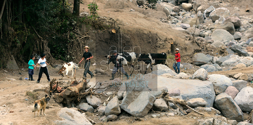 Villagers walk by rocks in the small Mayan town where 52 people were killed and six others went missing in five minutes on October 5 when a landslide tore through the village, leaving many boulders in its wake. Townspeople said no one from governmental or non-governmental agencies has visited the town since the disaster. Torrential rains associated with Hurricane Stan inundated parts of Central America in early October, causing flooding and mudslides across western Guatemala.<br />
