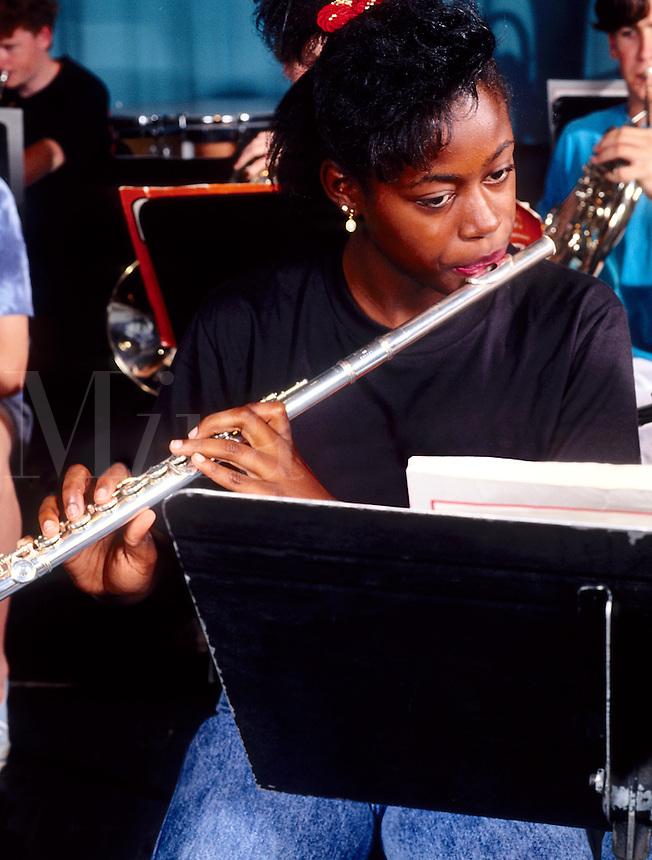 Black african american student practising iinstrument in high school band class at schoo