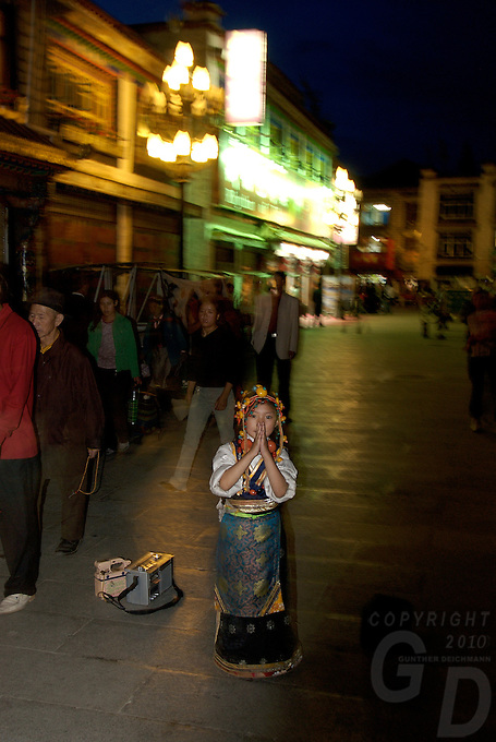Night scene little girl asking for a donation. Street life and scenes in Lhasa, Tibet