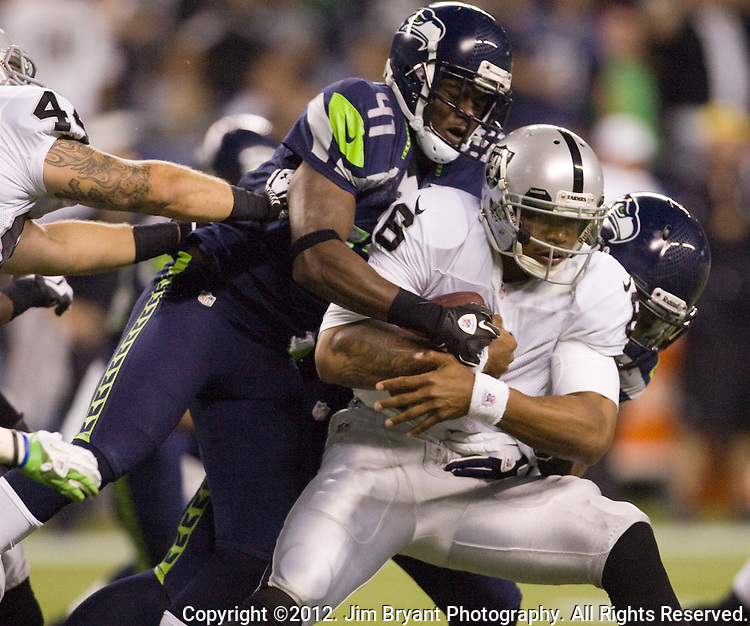 Oakland Raiders' quarterback Terrelle Pryor (R) is sacked by Seattle Seahawks' defensive end Chris Clemons in a pre-season game at CenturyLink Field in Seattle, Washington on August 30, 2012.©2012. Jim Bryant Photo. All Rights Reserved.