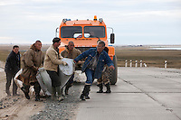 Bovanenkovo ,Yamal Peninsula, Russia, 09/07/2010..Gazprom workers and Nenets men lay insulation material across a new road to allow the Nenets sledges to cross as the indigenous nomadic reindeer herders head north on sledges to the Russian Arctic coast. The Nenets had previously been unable to follow their traditional migration routes because new roads constructed by Gazprom damage the sledges.