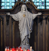 Sculpture of Christ with sacred heart, votive candles below, Eglise Saint-Sulpice (St Sulpitius' Church), c.1646-1745, late Baroque church on the Left Bank, Paris, France. Picture by Manuel Cohen