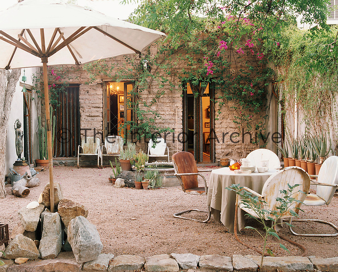 A tranquil gravelled courtyard garden is furnished with a collection of rusting chairs and decorated with an ornamental fountain