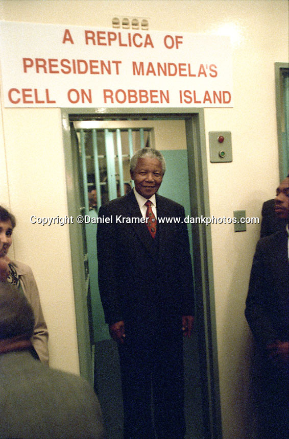 At the South African Parliament building in Cape Town, South African President Nelson Mandela officially opens an exhibit of a replica of his former jail cell on Robben Island. Also at the event was the then-current Robben Island Prison Choir.