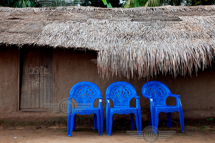 Blue plastic chairs outside a thatched hut.