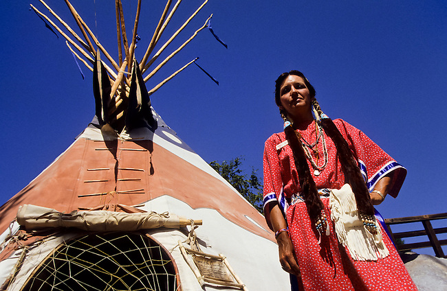 Indian woman in native dress next to tepee tent in California, USA