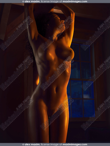 Beautiful nude woman standing naked by a wooden pillar in dim dramatic light with glittering skin