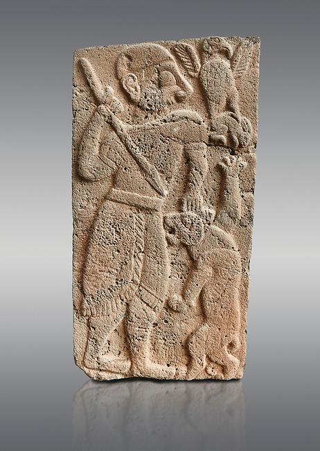 Pictures & images of the North Gate Hittite sculpture stele depicting Hittite God hunting a lion. 8th century BC. Karatepe Aslantas Open-Air Museum (Karatepe-Aslantaş Açık Hava Müzesi), Osmaniye Province, Turkey. Against grey background