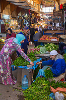 Fes, Morocco.  Woman Shopping for Mint from a Vendor in the Medina, Tala'a Kabira Street.
