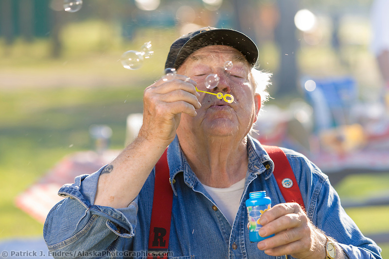 Old man blows bubblues on a summer day in Fairbanks, Alaska