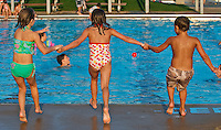Three children hold hands as they leap together into community swimming pool.