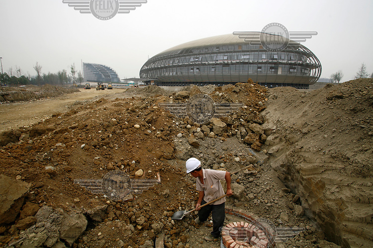 A worker digs a ditch on the construction site of the futuristic new City Hall complex. Chengdu has been picked as the centre for development in China's western region and has seen a rapid facelift as hundreds of millions of dollars pour into the city.