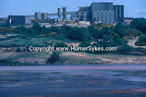 Wheal Jane tin mine near Baldhu and Chacewater in West Cornwall. Cornish Tin Mining Company. 1970s England. Slurry waste water lake in foreground. 1978